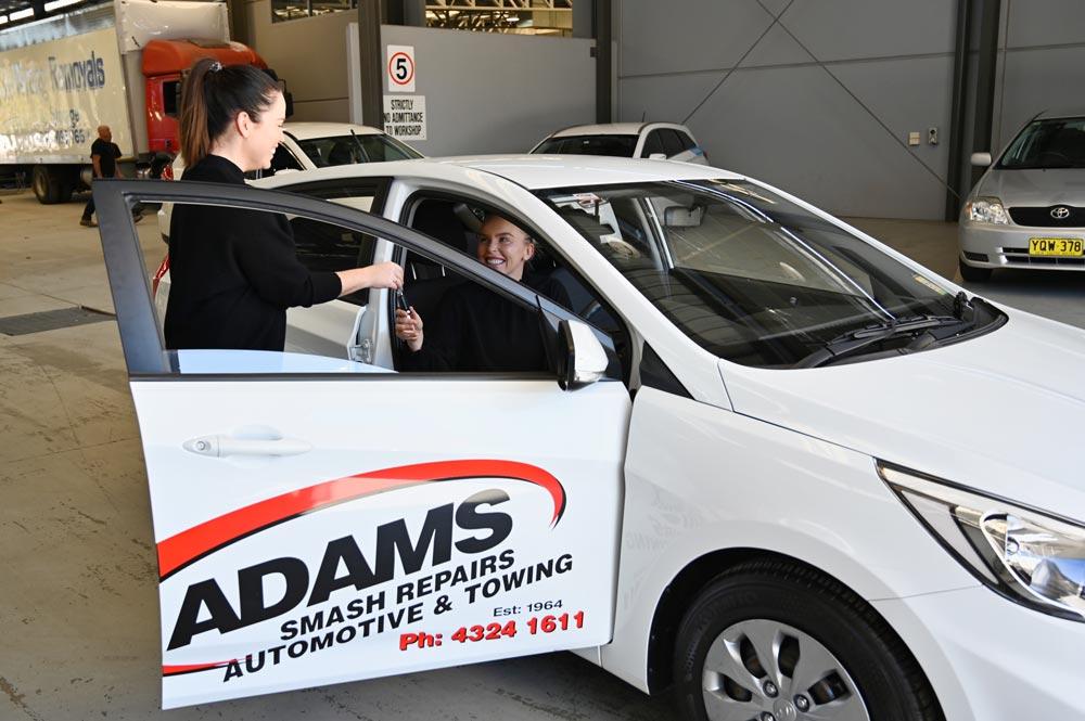 Adams Smash Repairs loan car with worker handing customer keys