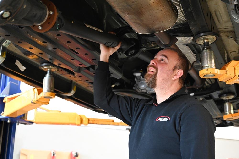 Adams Smash Repairs worker inspecting vehicle he is underneath