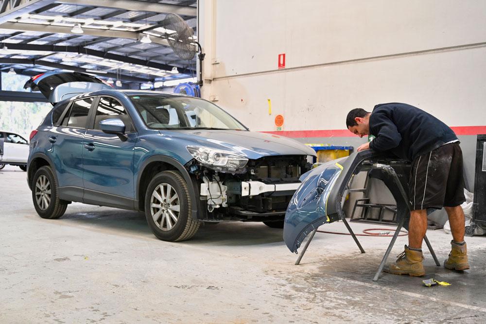 Worker repairing dismantled car bumper